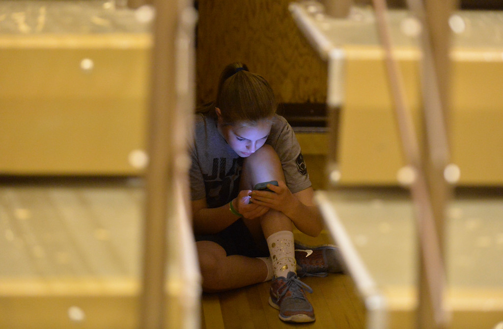 Justin Sheely | The Sheridan Press<br /> A girl looks at her phone under the bleachers during the Broncs basketball game Friday at Sheridan High School.