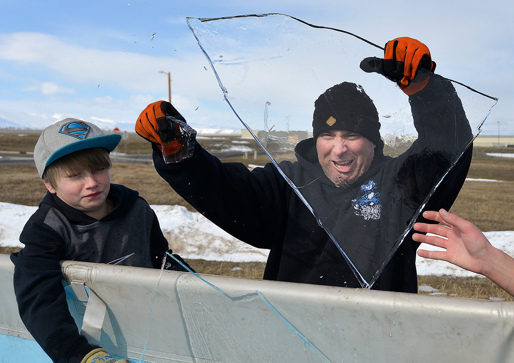 Justin Sheely | The Sheridan Press<br /> Fourteen-year-old Skyler Kilborn and Sheriff's Deputy Boot Hill react as a sheet of ice breaks away during preparation for the annual Jackalope Jump Saturday at Goose Valley Fire Department. A layer of ice formed over the pool overnight prior to the fundraising event. Special Olympics athletes, law enforcement agencies and volunteer firefighters jumped in the pool with at temperature of 38 degrees fahrenheit to raise money for the Wyoming Special Olympics.