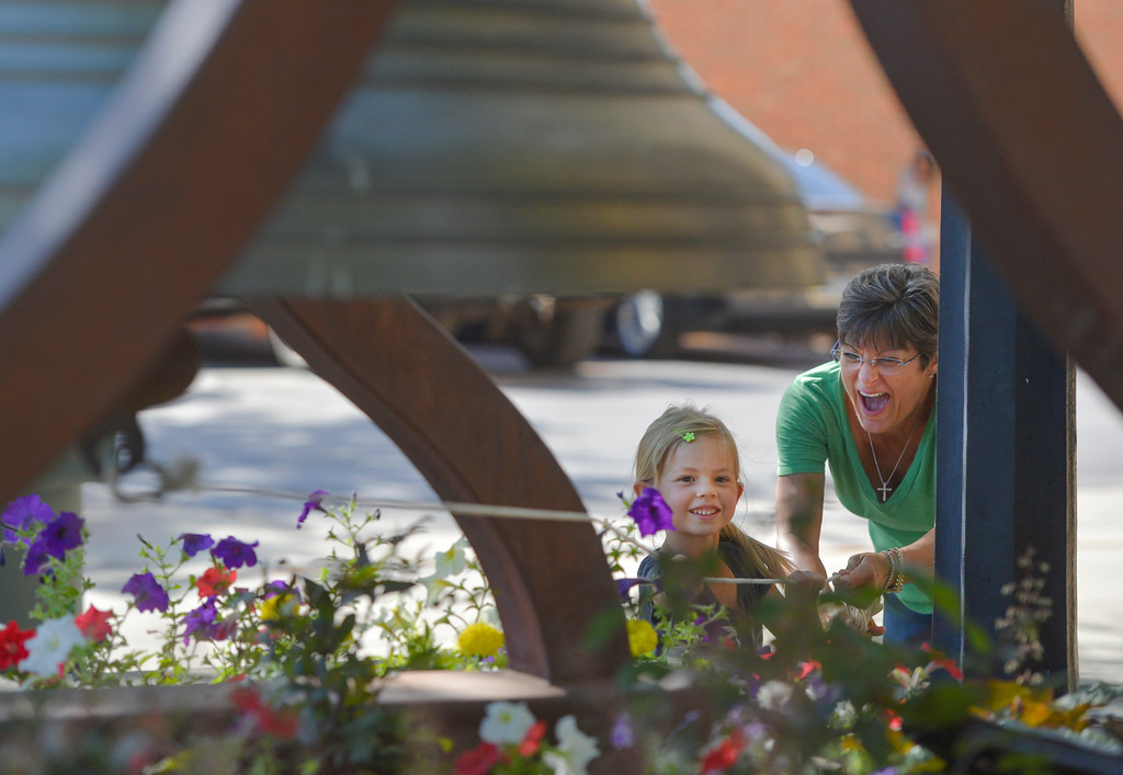 Justin Sheely | The Sheridan Press<br /> Aliyah Adams, left, and Cheryl Van Dyke ring the bell to signal the start of the Farmers Market Thursday on Grinnell Plaza.