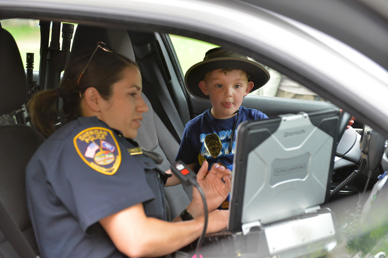Justin Sheely | The Sheridan Press<br /> Sheridan Police Officer Annalisa Jones shows four-year-old Sawyer Swindell the interior of her car during the 'Ice Cream with a Cop' outreach event at Kendrick Park Ice Cream. Sheridan Police Department held the event as part of their ongoing efforts to make positive impressions on Sheridan's youth.