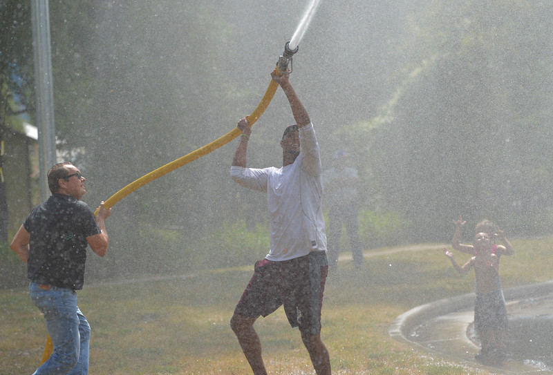 Justin Sheely | The Sheridan Press<br /> Curtis Schenderline, left, and Sergio Trocha aim their water hose at the barrel during the annual Firemen's Water Fight Saturday at Scott Park in Dayton.