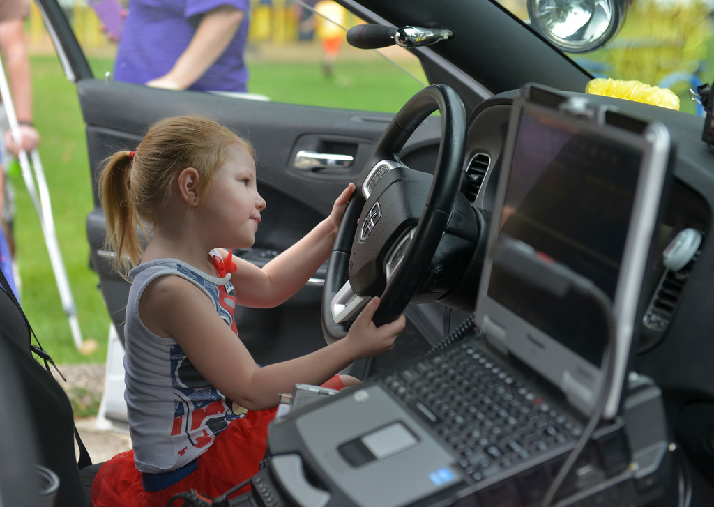 Justin Sheely | The Sheridan Press<br /> Three-year-old Piper Brown pretends to drive the cop cara during the 'Ice Cream with a Cop' outreach event at Kendrick Park Ice Cream. Sheridan Police Department held the event as part of their ongoing efforts to make positive impressions on Sheridan's youth.