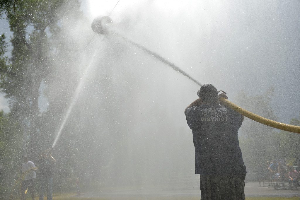 Justin Sheely | The Sheridan Press<br /> Teams aim their water hoses at the suspended barrel to move it to the other's side during the annual Firemen's Water Fight Saturday at Scott Park in Dayton.