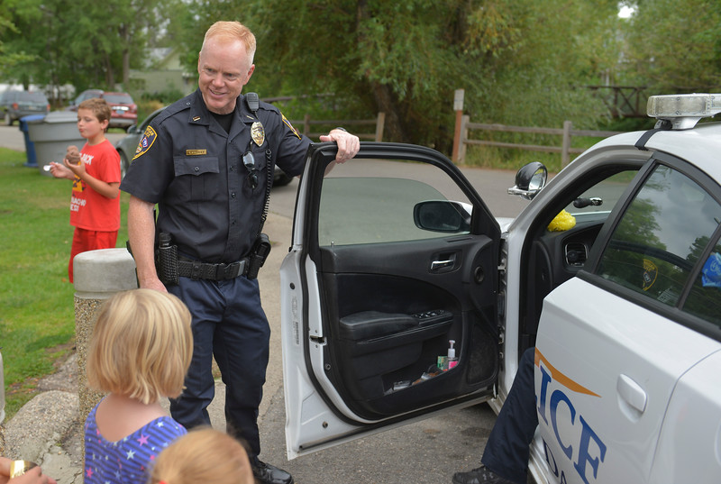Justin Sheely | The Sheridan Press<br /> Lt. Tom Ringley invites those gathered to see the police car during the 'Ice Cream with a Cop' outreach event at Kendrick Park Ice Cream. Sheridan Police Department held the event as part of their ongoing efforts to make positive impressions on Sheridan's youth.