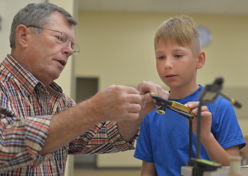 Justin Sheely | The Sheridan Press<br /> Volunteer Paul James helps Caden Anderson tie a sowbug fly bait during the Lifetime Activities Camp Thursday at Tongue River Elementary in Ranchester. Joey's Foundation lead fly tying and fly fishing workshops as part of the activity camp offered through the Tongue River Valley Community Center.