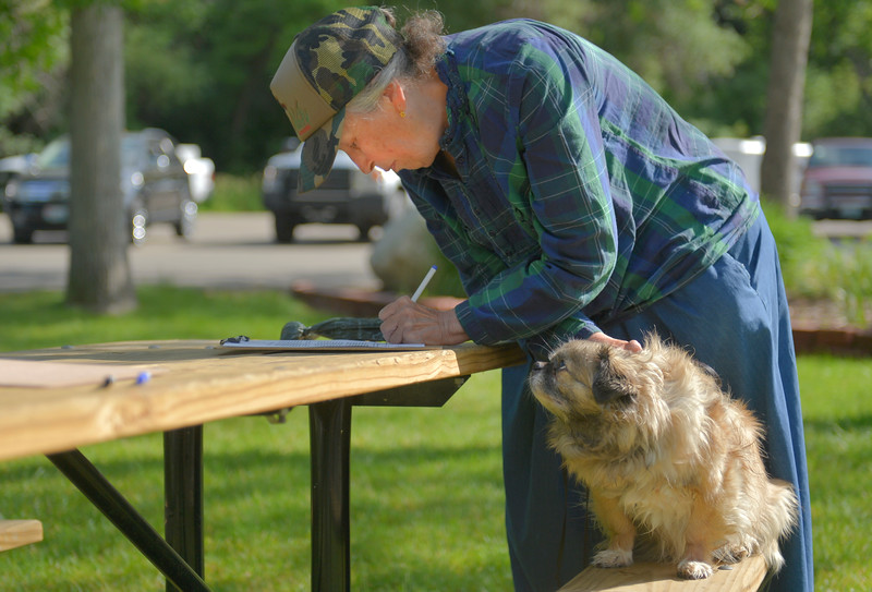 Justin Sheely | The Sheridan Press<br /> Zorro, a Tibetan Spaniel, looks at his owner Susan Love as she signs a waiver for a vaccination during the Sheridan Dog and Cat Shelter's annual rabies clinic Tuesday at Kendrick Park. The annual rabies clinic will take place in Kendrick Park June 6-10 from 8 a.m. to 1 p.m. Shots will be given by a veterinarian and cost $10 per animal.