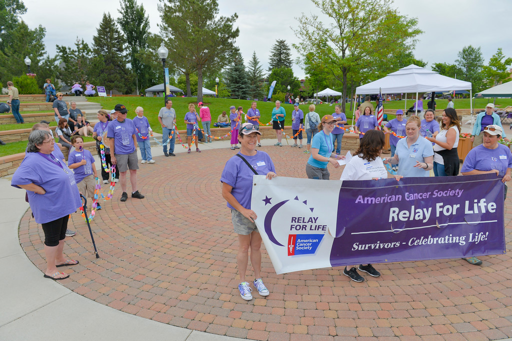 Justin Sheely | The Sheridan Press<br /> Survivors gather and hold the paper chain representing total years living with cancer during the annual Relay for Life event Saturday at Whitney Commons Park.