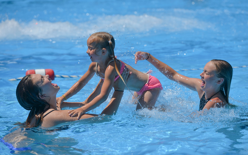 Justin Sheely | The Sheridan Press<br /> Sixteen-year-old Bailey Aksamit, left, catches Sierra Tracy, 6, from Bree Aksamit, 13, as they play in the water Wednesday at Kendrick Pool. The pool is open 1 - 7 p.m. daily, Sunday admission is only $1. The pool closes for the season August 26.