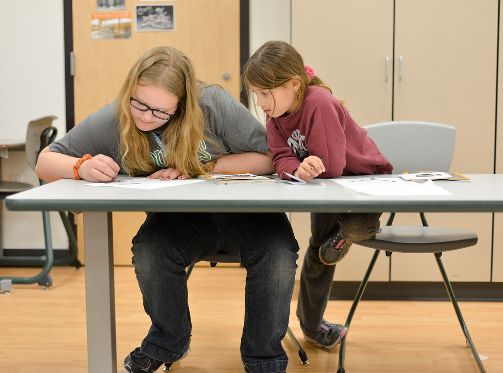 Justin Sheely | The Sheridan Press<br /> Fifth-graders Katrena Nelson, left, draws with charcoal as Aspen Weber looks on in a mixed media arts class during the after school program Tuesday at Coffeen Elementary School. Students learned about the values in the gray scale and followed various exercises including pulling a photo from a magazine, placing a viewfinder over a picture then creating a charcoal drawing from the image within the frame.
