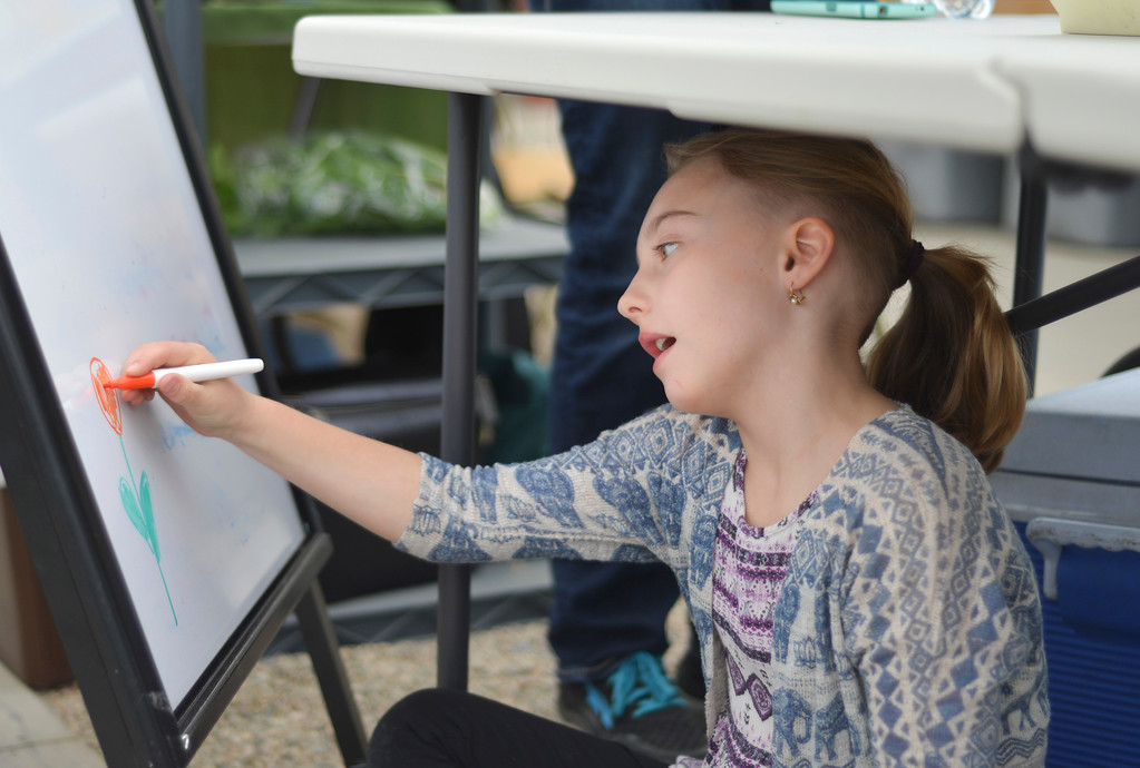Justin Sheely | The Sheridan Press<br /> Nine-year-old Aira Wesnitzer doodles on a vendor's whiteboard during the Farmers Market Saturday at Landon's Greenhouse. The market has been running throughout the winter and spring every Saturday from 10 a.m. to noon.