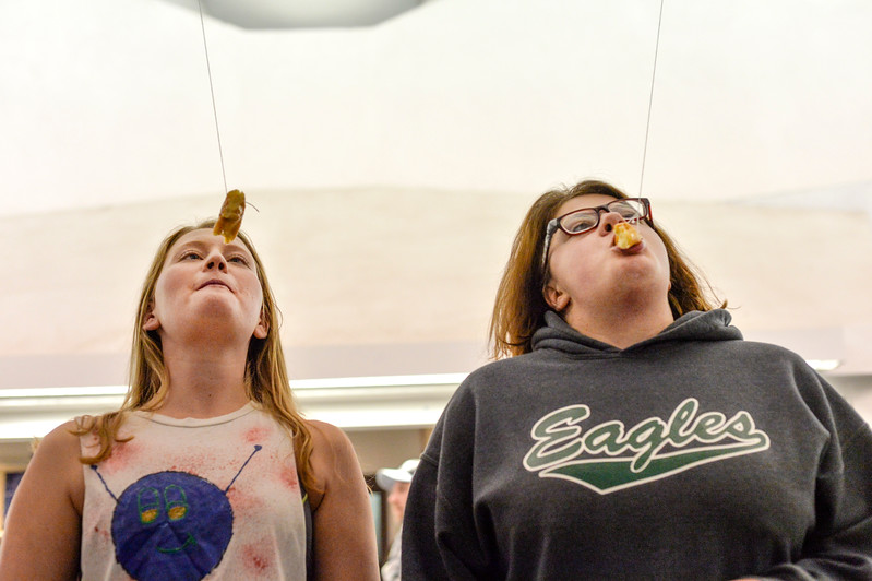 Justin Sheely | The Sheridan Press<br /> College students Allison Reed, left, and Lyndsey Black race to eat donuts from strings during the carnival Saturday in the Bruce Hoffman Golden Dome at Sheridan College.