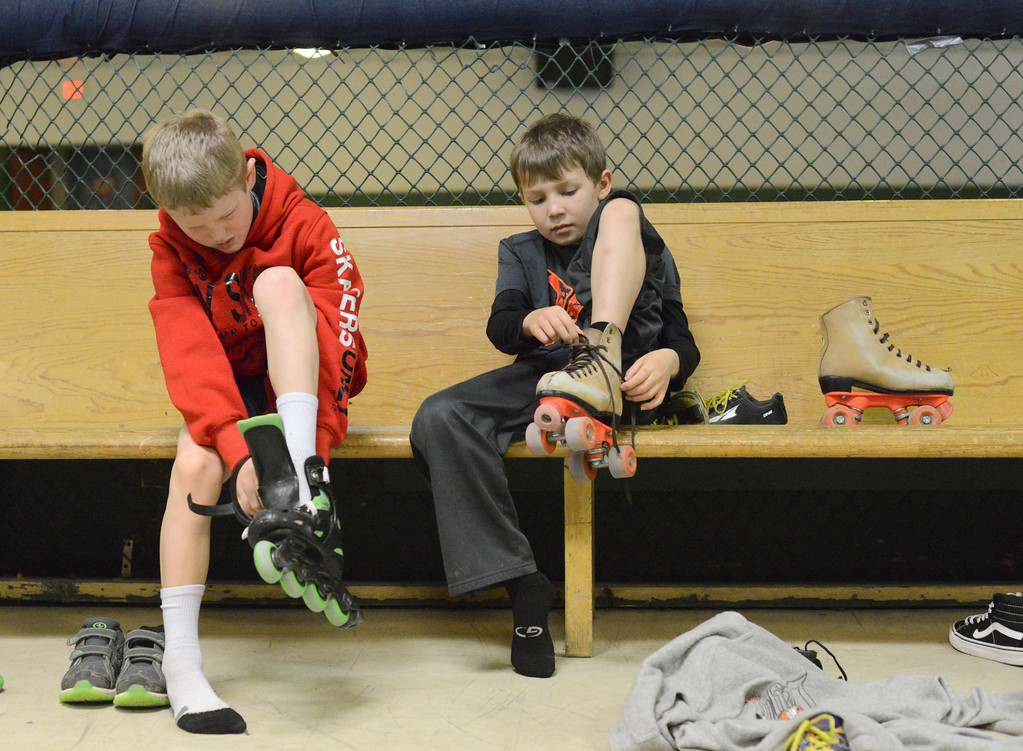 Justin Sheely | The Sheridan Press<br /> Second-graders Ayden McInerney, left, and Nailin Fletcher put on skates during the YMCA's Big Horn Fun Day program at Scotty's Skate Castle Friday morning. The YMCA offers fun activities for children who go to Big Horn schools since Sheridan County School District 1 does not hold class on Fridays.