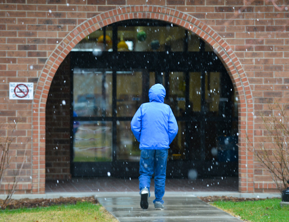 Justin Sheely | The Sheridan Press<br /> A person walk under a wintry mix Tuesday morning at the Sheridan County Fulmer Public Library.
