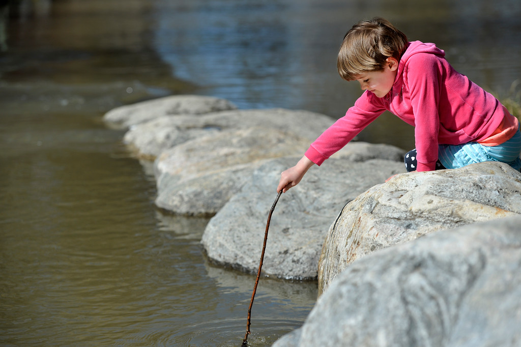 Justin Sheely | The Sheridan Press<br /> Five-year-old Freya O'Bryan-Herriott plays in the Big Goose Creek on a sunny Wednesday morning at Kendrick Park. The next several days hold chances for rain with possibility for snow.