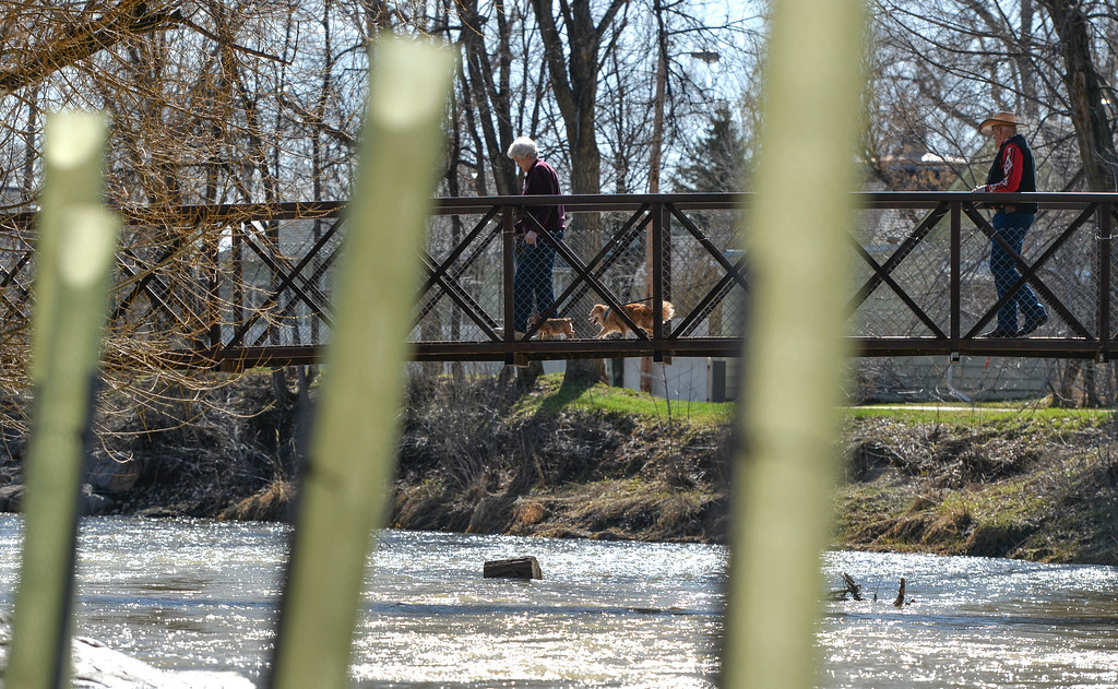 Justin Sheely | The Sheridan Press<br /> People cross the Big Goose Creek on a sunny Wednesday morning at Kendrick Park. The next several days hold chances for rain with possibility for snow.