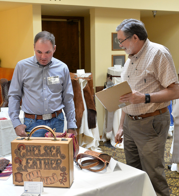 Justin Sheely | The Sheridan Press<br /> Show judges Barry King of Sheridan, left, and Jim Linnell of Venus, Texas, look over entries of the competition during the annual Rocky Mountain Leather Crafters Trade Show Friday at the Sheridan Inn Convention Center.