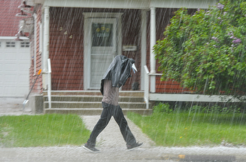 Justin Sheely | The Sheridan Press<br /> A pedestrian is caught under pea-sized hail Wednesday afternoon on Coffeen Avenue. The National Weather Service has issued a flood advisory for small stream areas in Sheridan County.
