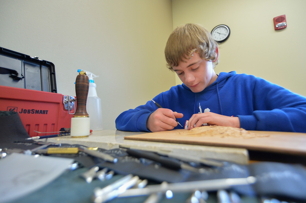 Justin Sheely | The Sheridan Press<br /> Sixth-grader Justin Tope of Rozet, Wyoming, works on his extreme emboss project in a workshop during the Rocky Mountain Leather Crafters convention Thursday at Sheridan College. The week-long annual convention draws tradesmen and women from across the globe to Sheridan Wyoming to learn techniques and skills in leather crafting, shaping and tooling.