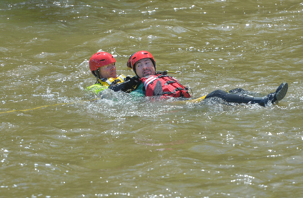 Justin Sheely | The Sheridan Press<br /> Goose Valley volunteer firefighters Justin Johnston, left, rescues Ben Weaver from the water during a swift water rescue training exercise Saturday on the Goose Creek by Thorne-Rider Park. The firefighters keep their feet up to avoid getting caught on the bottom of the creek and pulled under water. The exercise was to teach basic skills in defensive swimming and floating in a river to avoid being pulled under the current. Personnel also practiced how to throw ropes from the embankment to persons in the water. Participating agencies included Sheridan Fire-Rescue, Goose Valley Fire Department, Story Fire Department and Rocky Mountain Ambulance.