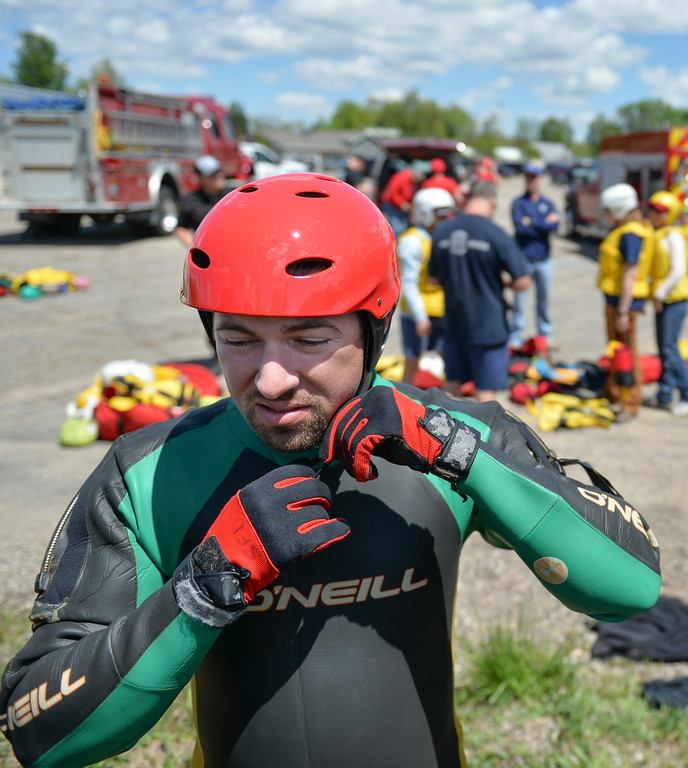 Justin Sheely | The Sheridan Press<br /> Goose Valley volunteer firefighter Ben Weaver puts on a helmet and wetsuit during a swift water rescue training exercise Saturday on the Goose Creek by Thorne-Rider Park. The exercise was to teach basic skills in defensive swimming and floating in a river to avoid being pulled under the current. Personnel also practiced how to throw ropes from the embankment to persons in the water. Participating agencies included Sheridan Fire-Rescue, Goose Valley Fire Department, Story Fire Department and Rocky Mountain Ambulance.