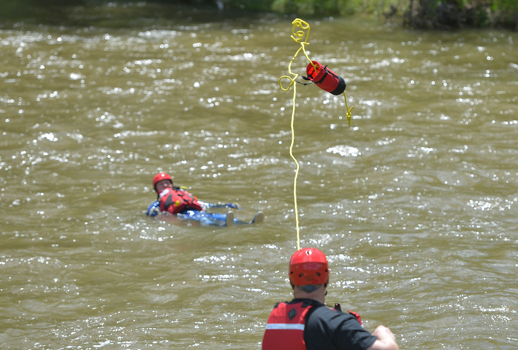 Justin Sheely | The Sheridan Press<br /> A first responder throws a rope to a Goose Valley volunteer firefighter during a swift water rescue training exercise Saturday on the Goose Creek by Thorne-Rider Park. The exercise was to teach basic skills in defensive swimming and floating in a river to avoid being pulled under the current. Personnel also practiced how to throw ropes from the embankment to persons in the water. Participating agencies included Sheridan Fire-Rescue, Goose Valley Fire Department, Story Fire Department and Rocky Mountain Ambulance.