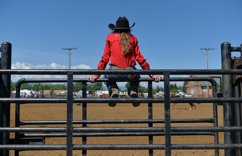 Justin Sheely | The Sheridan Press<br /> A Sheridan County student sits on the gate as a barrel racer competes during the Sheridan County high school rodeo Monday at the Sheridan County Fairgrounds.