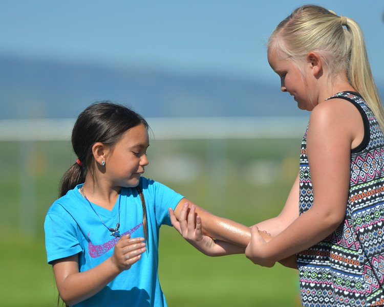 Justin Sheely | The Sheridan Press<br /> Third-grader Kaydence Morris, left, lets Joni Simonson rub sunscreen on her arm during the end of school play day Wednesday at Tongue River Elementary School. The play day celebrates the end of the school year and was themed around school principal Hofmeier – who retires this week.