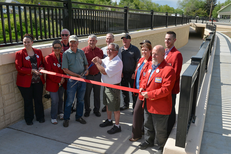 Justin Sheely | The Sheridan Press<br /> Pathway System committee member Bruce Pryde, left, and former Mayor Jim Wilson hold the scissors over the ribbon with ambassadors from the Sheridan County Chamber of Commerce during the ribbon cutting ceremony of the pedestrian underpass at 5th Street. To the right of Pryde, Mayor Roger Miller, Sen. Dave Kinskey, and Scott Taylor. The $2.2 million underpass connects 8.5 miles of pathway with 10.5 miles of the pathway system. Previously pedestrians and bicyclists has to go down to Val Vista to safely cross 5th Street.
