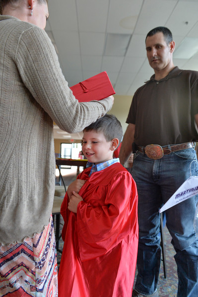 Justin Sheely | The Sheridan Press<br /> Six-year-old Joseph Panetta stands between his parents Shiann Panetta and E.J. Panetta as they get him ready during the Children's Center annual Preschool Graduation Tuesday at Sheridan Wesleyan Church. The Children's Center had 35 students graduate, which is the largest group the preschool held.