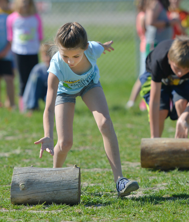 Justin Sheely | The Sheridan Press<br /> Second-grader Janie McDonald pushes log for a race during the end of school play day Wednesday at Tongue River Elementary School. The play day celebrates the end of the school year and was themed around school principal Hofmeier – who retires this week.