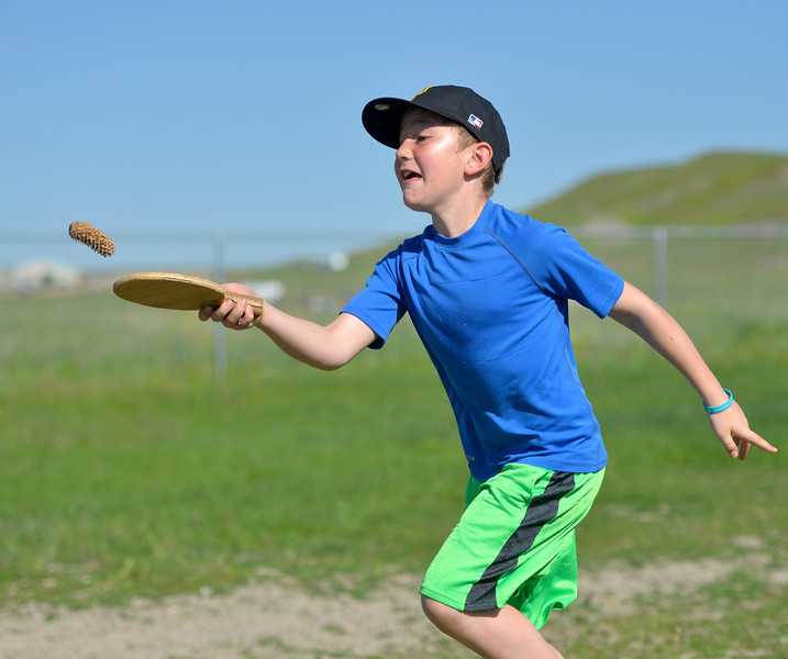 Justin Sheely | The Sheridan Press<br /> Third-grader Isaac Fritz runs a relay race while balancing a pinecone on a paddle during the end of school play day Wednesday at Tongue River Elementary School. The play day celebrates the end of the school year and was themed around school principal Hofmeier – who retires this week.