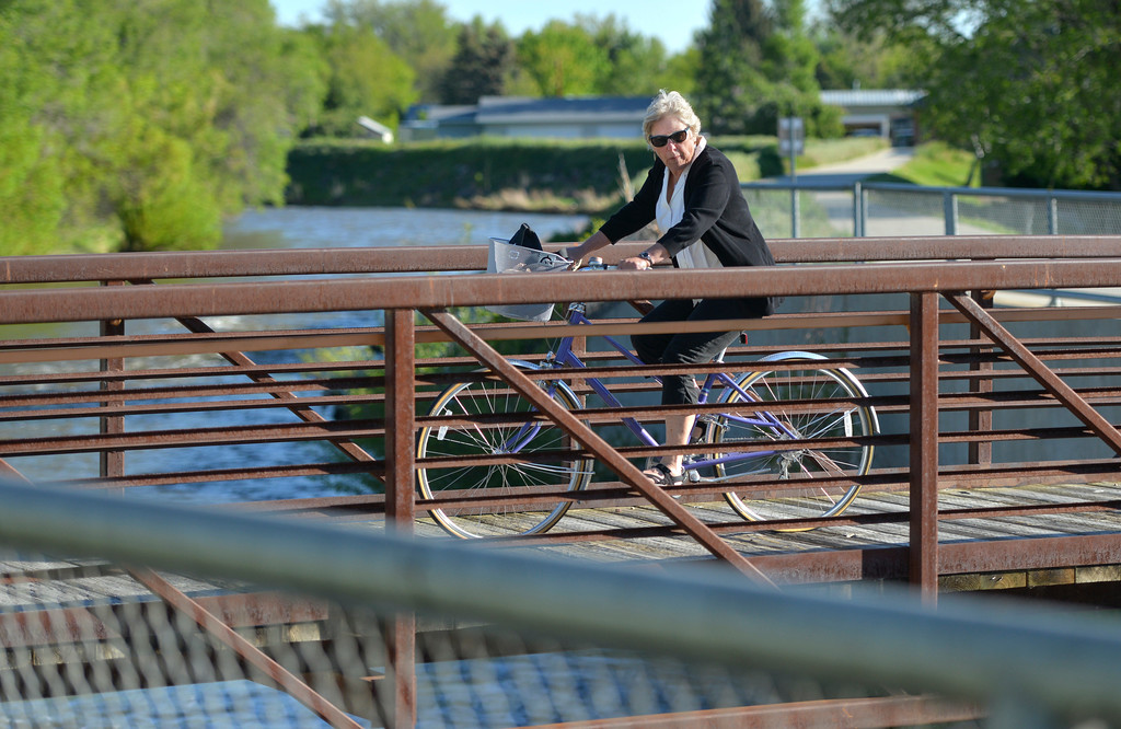 Justin Sheely | The Sheridan Press<br /> A woman rides her bicycle across a bridge over the Goose Creek Tuesday morning. Tuesday's high will be 69, Wednesday will be 80 according to the National Weather Service.