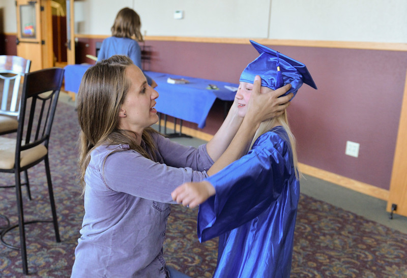 Justin Sheely | The Sheridan Press<br /> Jessie Koltiska puts a cap on her daughter Finnley Koltiska, 5, during the Children's Center annual Preschool Graduation Tuesday at Sheridan Wesleyan Church. The Children's Center had 35 students graduate, which is the largest group the preschool held.