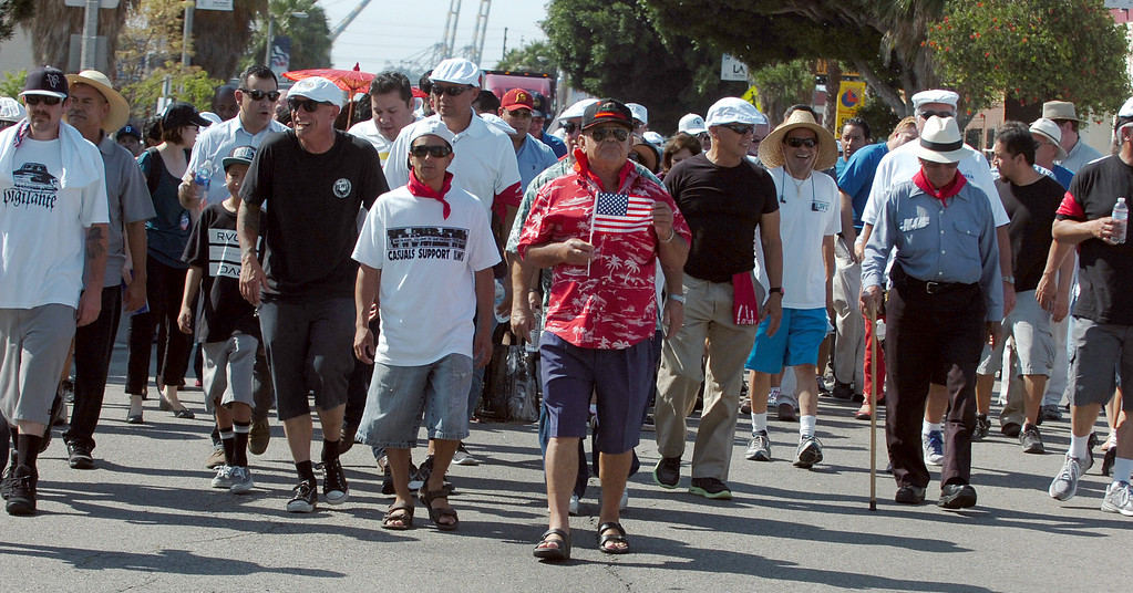 . George Ruano, of Norwalk, carries the American flag as he marches with other union workers and supporters on Avalon Boulevard as they celebrate in the 34th annual Harbor Labor Day March and Rally in Wilmington September 2, 2013. (Thomas R. Cordova/Staff Photographer)