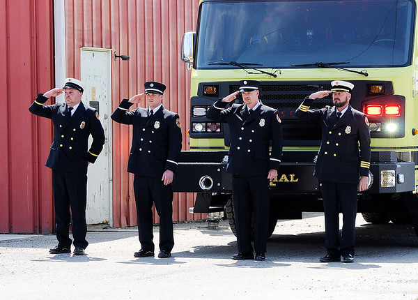 Don Knight | The Herald Bulletin<br /> Gas City firefighers salute in front of their ladder truck that was set up to display the flag in front of Pipe Creek's Fire Department on Ind. 28 on Wednesday.