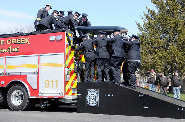 Don Knight | The Herald Bulletin<br /> Firefighters lift David Wittkamper onto Pipe Creek's Engine 1 for a procession through Elwood on Wednesday.