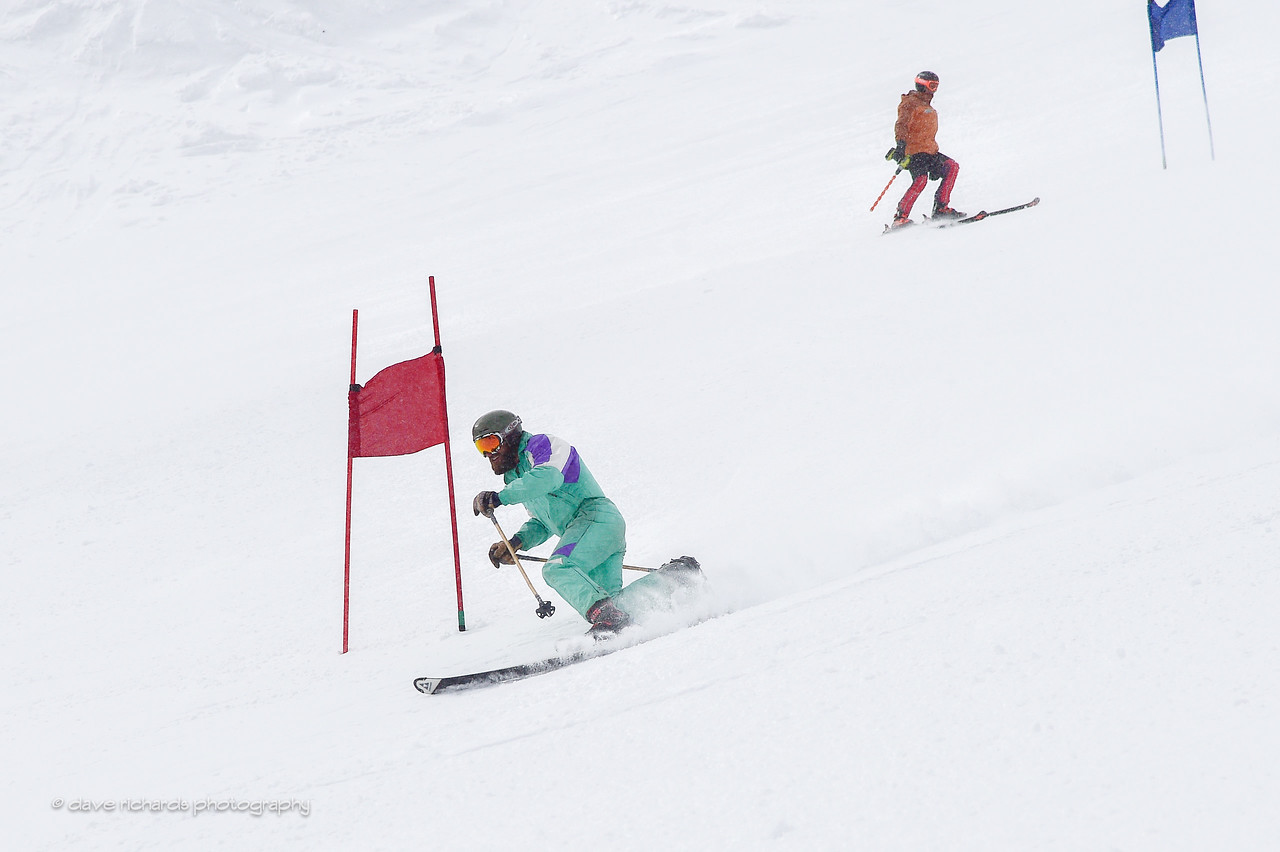 Telemark racer followed by course worker making repairs to the race gates. 2017 Alta Town Race - GS#8 (Photo by Dave Richards, daverphoto.com)
