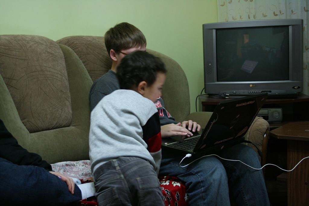 Emi watching Daniel's computer.