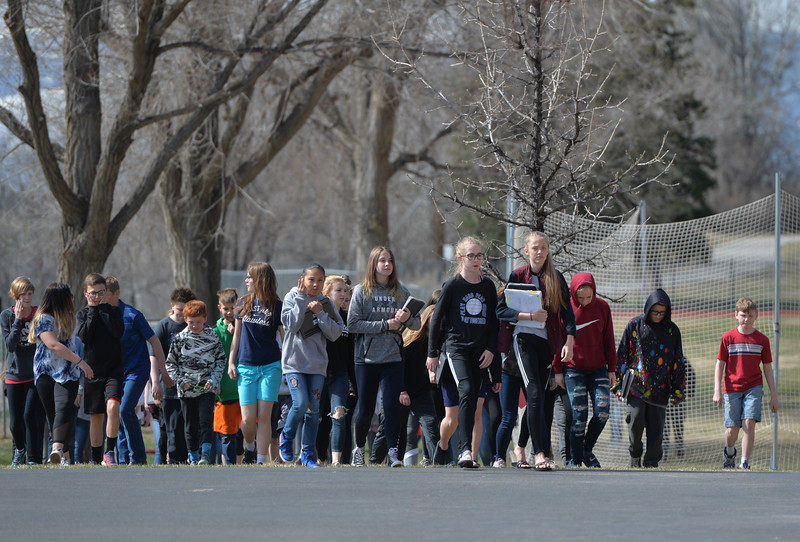 Justin Sheely | The Sheridan Press<br /> Middle school students walk to the front doors of the building to return to class during the organized walkout at Sheridan Junior High School Friday, April 20, 2018. More than 60 students were part of the National School Walkout, which was started by four high school students in Connecticut and aims to engage students to hold elected officials accountable and end gun violence in schools.