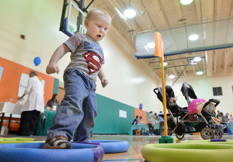 Justin Sheely | The Sheridan Press<br /> Two-year-old Caleb Rigdon steps through a series of hoops and obstacles during the inaugural Early Childhood Children's Festival at the YMCA Saturday, April 14, 2018. The adaptive station promoted problem solving and motor skills. The event was a collaboration with various community early childhood education organizations to bring awareness to the importance of early childhood education at kindergarten readiness.