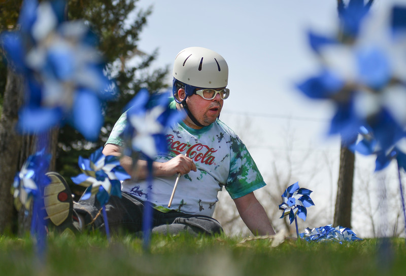 Justin Sheely | The Sheridan Press<br /> Scott Halladay pushes pinwheels in the ground at the Sheridan County Courthouse Thursday, April 19, 2018. Volunteers from various local organizations planted the pinwheel gardens to bring awareness that April is National Child Abuse Prevention Month.