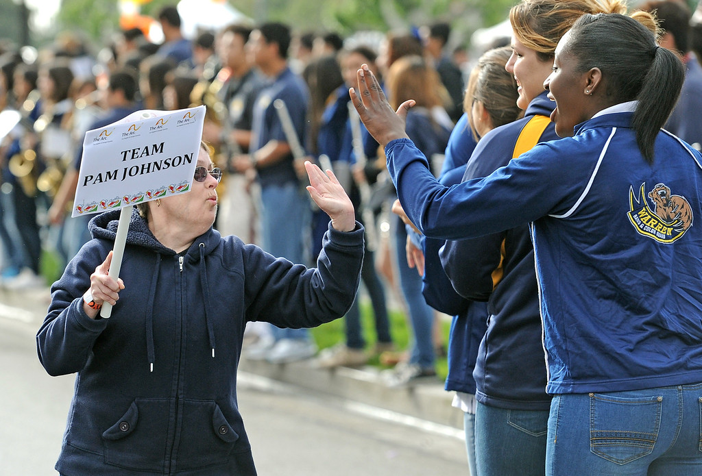 . Pam Johnson, left, high-fives Diamond Lee of the Warren High School Color Guard along the route of the Arc Walk for Independence at the Stonewood Center in Downey, CA. on Saturday March 22, 2014. (Photo by Sean Hiller/ Daily Breeze).