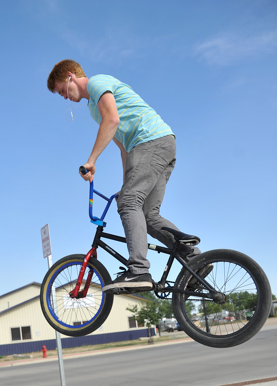 Chase Mugridge does a 360-degree jump on his trick bike on North Main Street Saturday in Sheridan. Mugridge recently moved from Michigan to live with his father. (The Sheridan Press/Justin Sheely)