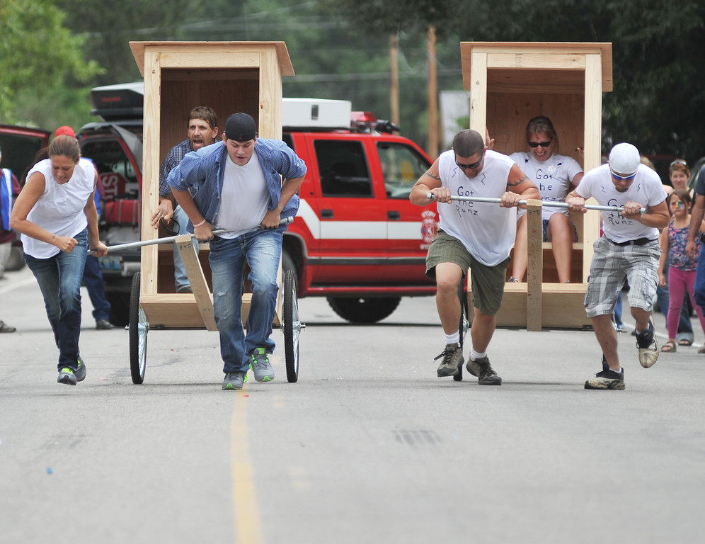 Teams compete in Outhouse Chariot Racing during Story Days Saturday, Aug. 24, 2013. From left, Dianna Murphy, Matt Paumer, and Rickie Huffman fall behind Dustin Quillen, Rebecca Quillen, and Wyatt Schrank of team 'Got the Runz' who won the race with a time of 43.91 seconds. (The Sheridan Press/Justin Sheely)