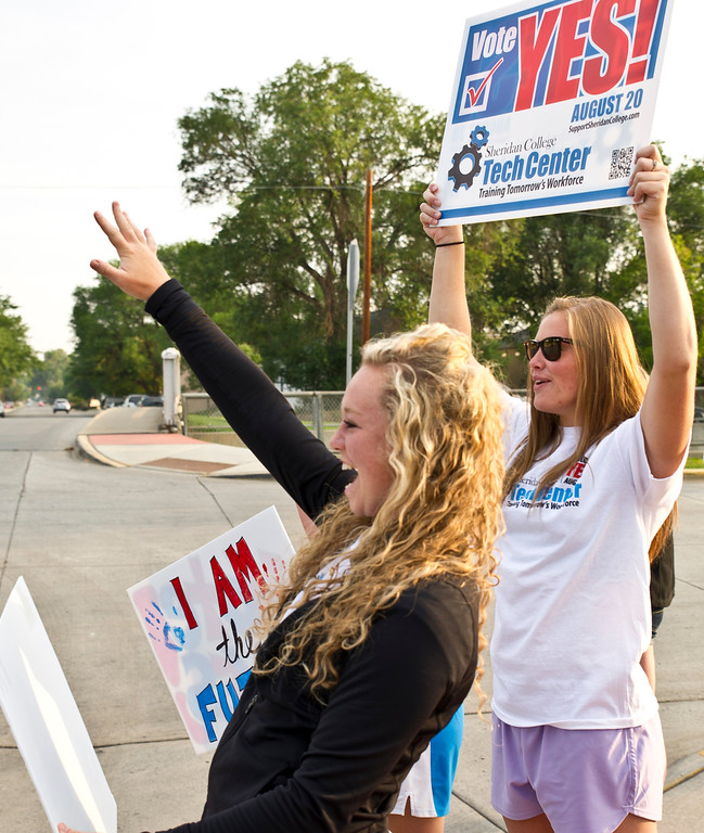 Sheridan College sophomore Hartley Stewart, left, and freshman Baylee Baker cheer as a motorist honks in support at the corner of Dow and Brooks Street Tuesday, August 20. The $15.8 million general issue bond for the Sheridan College Tech Center is on the ballot in this special election. (The Sheridan Press/Justin Sheely)