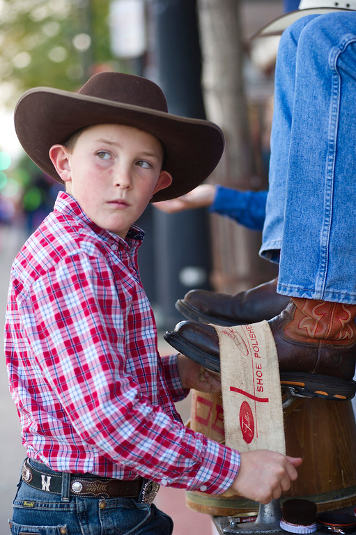 Sam Gregory buffs a cowboy's boot on his shoe shining station during the Third Thursday street festival on Main Street. Gregory and his brother learned the trade from their uncle and have been shining boots at the street festival during the summer. (The Sheridan Press/Justin Sheely)