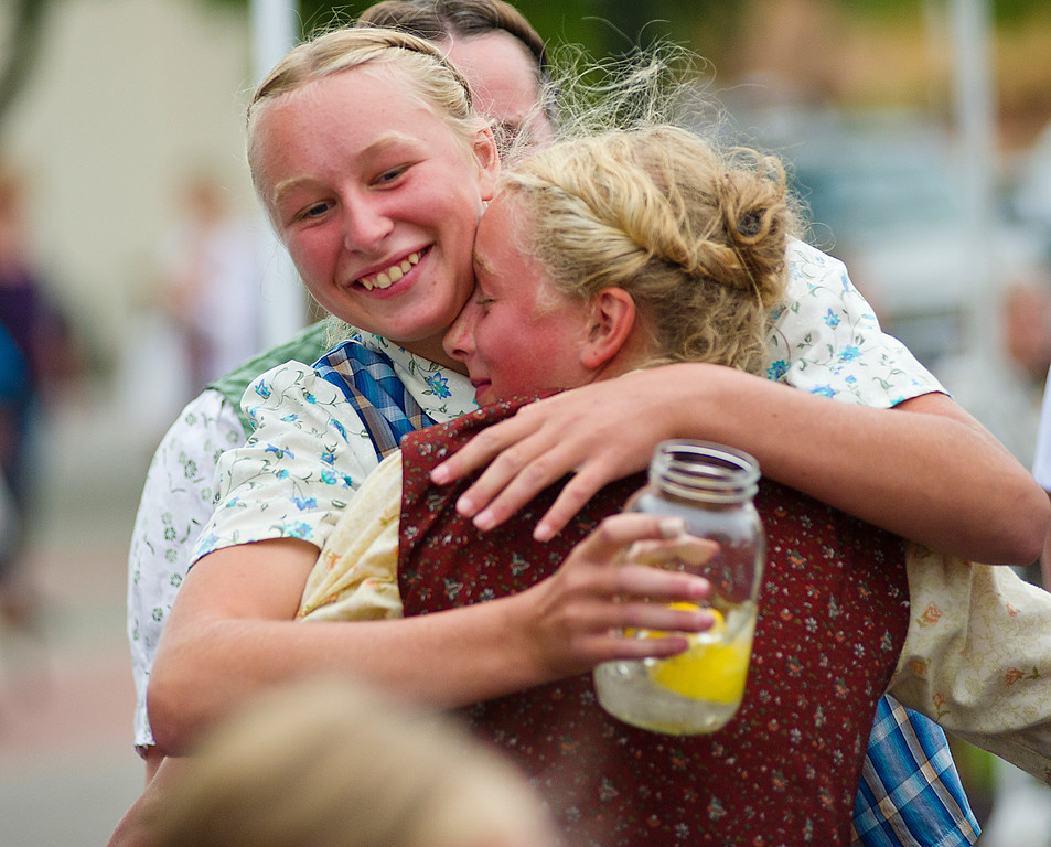 Joyce Walter, left, hugs her sister Carolyn Walter, from 40 Mile Colony Ranch near Lodge Grass, Mont., after Carolyn won the watermelon eating contest during the Farmers Market Thursday on Grinnell Plaza. (The Sheridan Press/Justin Sheely)