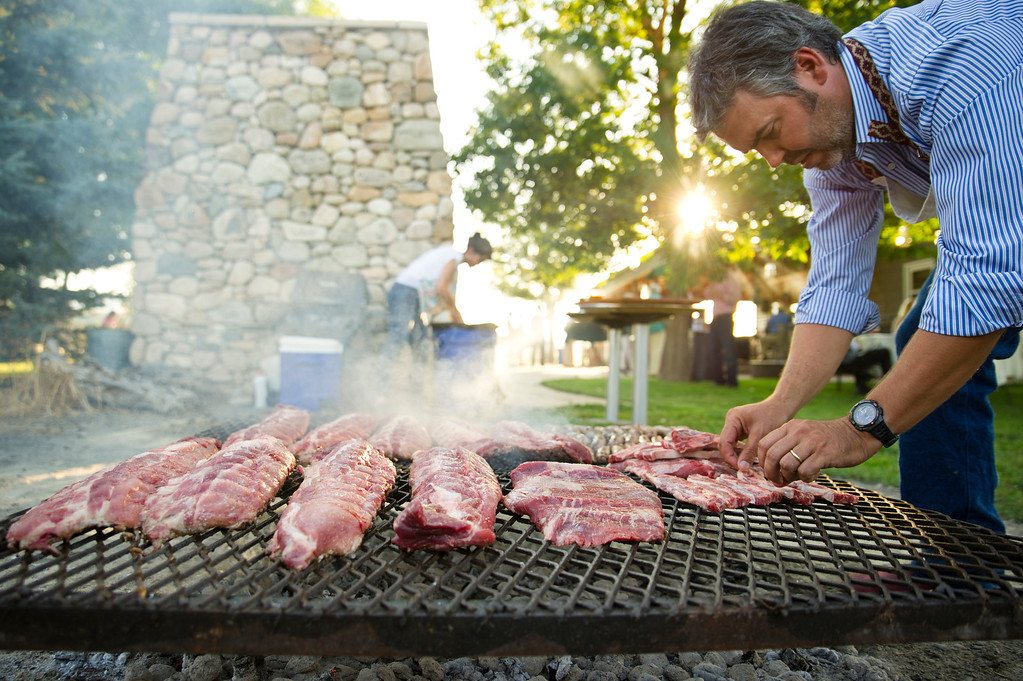 "Sebastian Mariani places strips of beef on an Argentine grill during the ""Jazz Along the Big Horns"" fundraiser Saturday, July 20, for the Big Horn Equestrian Center. The funds from the fundraiser go towards lease and maintenance costs of the 80-acre field. (The Sheridan Press/Justin Sheely)"
