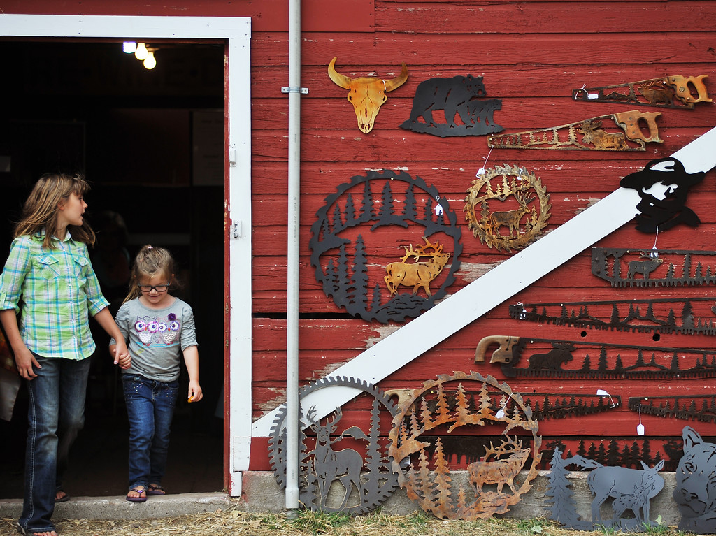 10-year-old Ellie Williams, left, guides Dylan Coon, 3, out of the barn to a wall full of circular and straight saws made into art during the 'Born in a Barn' vintage fall sale Friday at the Barn on Highway 14 East. Vendors sold items that were antique, refurbished, reimagined or handmade. (The Sheridan Press/Justin Sheely)