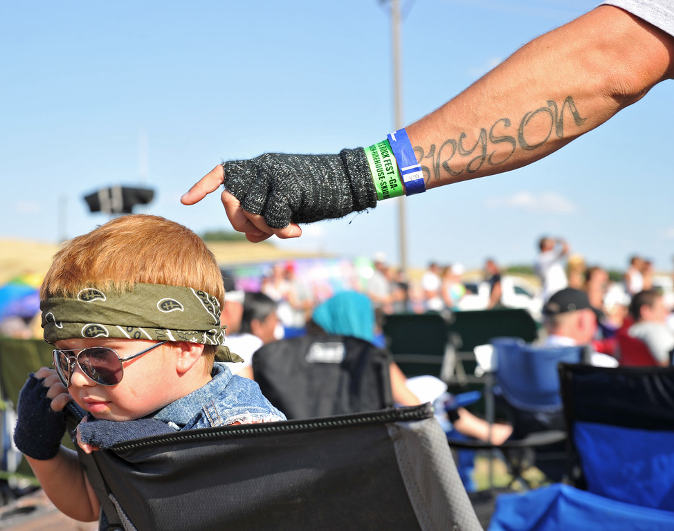 A distracted Bryson Adsit, 3, is receives a tap from his father while at the 80's Rock Fest at the Trails End Concert Park Saturday, Aug. 24, 2013. (The Sheridan Press/Justin Sheely)